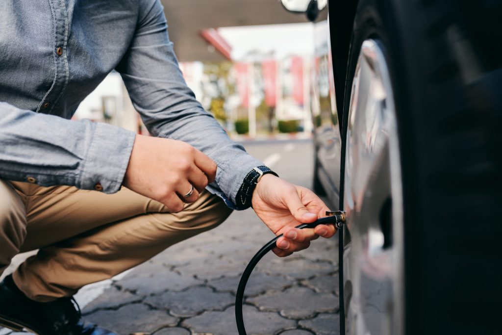 Man learning how to inflate car tires at gas station