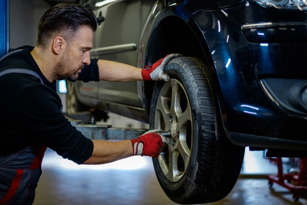 Mechanic putting lug nuts of tire back on